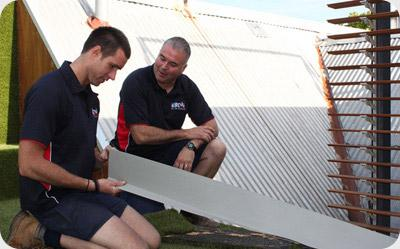 Two maintenance men completing roof work