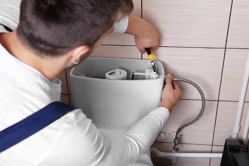 Plumber fixing toilet pipes